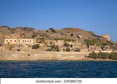 Cruise to the island of Spinalonga. Small boat on the blue lagoon. Spinalonga fortress on the island of Crete, Greece. Architecture on the island.