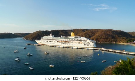 Cruise liner in the bay. View of a magnificent white  liner in a colorful bay of the among beautiful nature. Huatulco, Mexico .