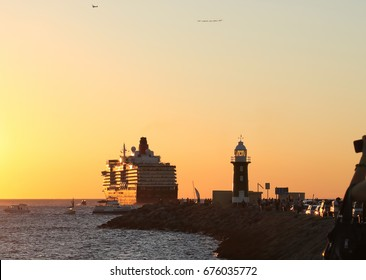 Cruise liner departing port at sunset