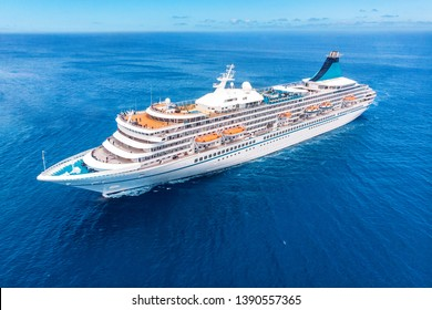 Cruise liner ship in ocean with blue sky. Aerial top view.