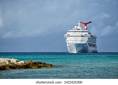 Cruise liner standing on anchor at sea near the  island. Funnel in traditional Red Blue and white colors. Carnival Cruise Lines. Carnival Liberty. Half moon key, Bahamas. march 2018