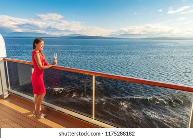 Cruise luxury travel lifestyle woman on fancy Europe vacation. Asian elegant lady drinking champagne glass watching sunset on private balcony deck.