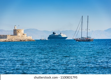 Cruise ship behind lighthouse in Mandraki harbor in City of Rhodes (Rhodes, Greece)