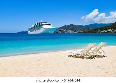 Cruise ship in Caribbean Sea with beach chairs on white sandy beach. Summer travel concept.