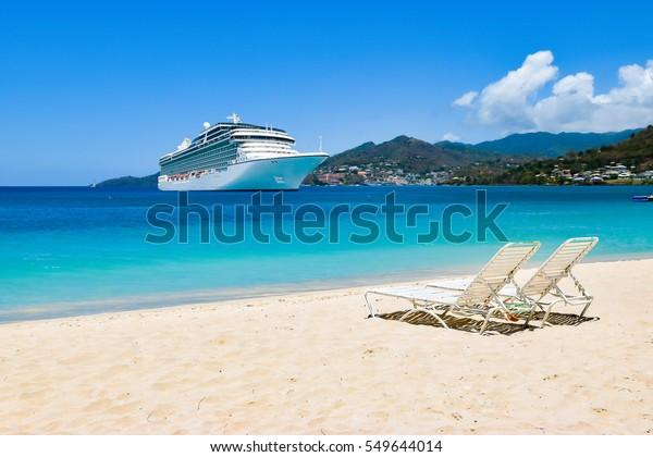 Kreuzfahrtschiff in der Karibik mit Liegestühlen auf weißem Sandstrand. Sommerreisekonzept.