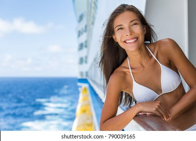 Cruise ship Caribbean travel vacation Asian woman tourist in bikini enjoying deck on troipcal holiday. Smiling happy girl having fun on boat. Portrait lifestyle.