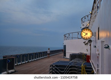 Cruise ship deck in evening with illuminated clock