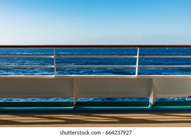 Cruise ship deck railing background with a deep blue ocean and clear blue skies and copy space