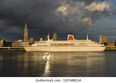 Cruise ship docked in Antwerpen, Belgium in front of the skyline line during sunset
