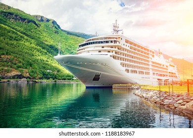 The cruise ship docked on a marina in the fjords at sunset.