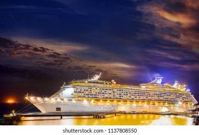 Cruise ship docked at port on sunset.