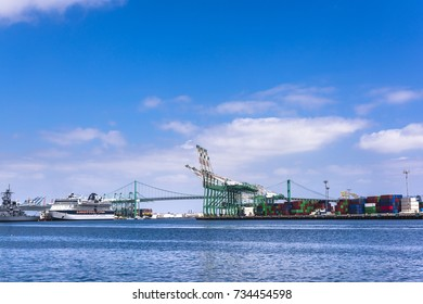 A cruise ship docked in ports of call in Long Beach California shows a heavy commerce transportation hub during a bright, sunny day.