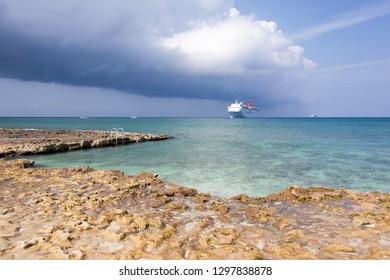 The cruise ship drifting near rocky Seven Mile beach on Grand Cayman island (Cayman Islands).