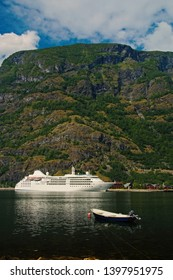 cruise ship at flam. Boat and cruise ship in sea on mountain landscape in Flam, Norway. Sea vessels in harbor with green mountains. Travelling by water. Summer vacation and holiday. Wanderlust and