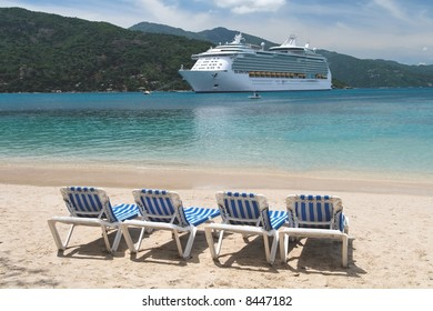 Cruise ship with four deck chairs in the foreground