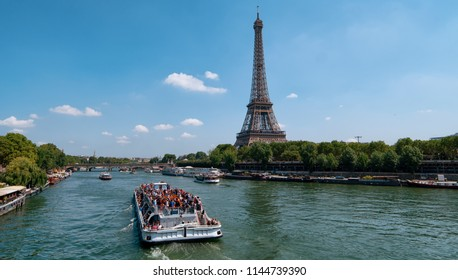 cruise ship full of tourists passing the Eiffle Tower