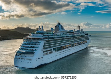 Cruise ship heading out to sea at sunset leaving caribbean island