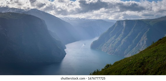 Cruise ship inbetween mountain cliff in fjord sunlight haze Norway