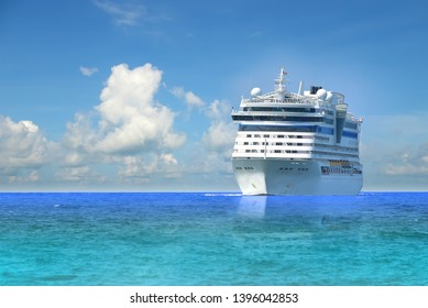 Cruise ship, large luxury white cruise ship liner on blue sea water and cloudy sky background.