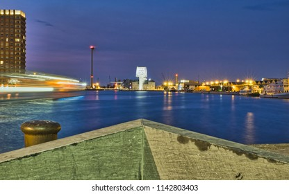 Cruise ship is leaving a dock in Antwerp, Belgium. In the background the beautiful 'Havenhuis' of Antwerp.