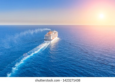 Cruise ship liner goes into horizon the blue sea leaving a plume on the surface of the water seascape during sunset. Aerial view, concept of sea travel, cruises