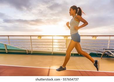 Cruise ship passenger doing morning jogging on deck running tracks with sunrise sunshine. Woman tourist enjoying fitness training during Caribbean travel vacation.