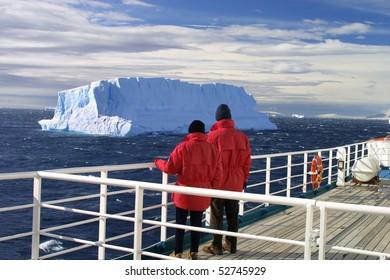 Cruise ship passengers looking at a beautiful iceberg at Antarctica