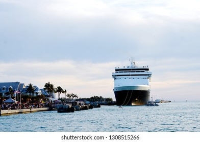 A cruise ship is in port as a crowd of people gather for the nightly Sunset Celebration at Mallory Square in Key West, Florida.