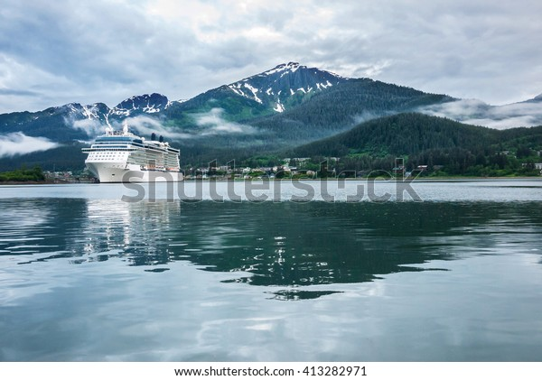 Cruise ship at a port in Juneau, Alaska with snow capped mountain and low lying fog in the background