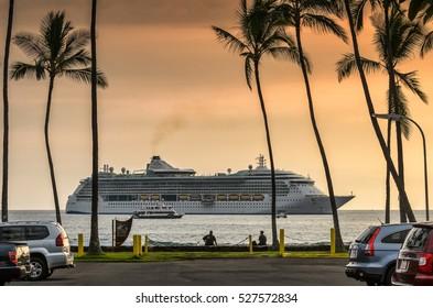 Cruise ship sailing, arriving to tropical island as seen from parking lot with palm trees at sunset