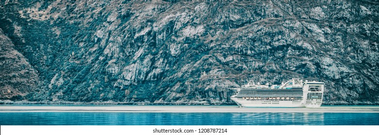 Cruise ship sailing at Glacier Bay, Alaska, on blue glacial ocean water and icebergs. Panoramic banner of Arctic travel background. Luxury vacation.