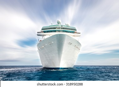 Cruise ship sailing in ocean, white liner on blue sea with blurred sky
