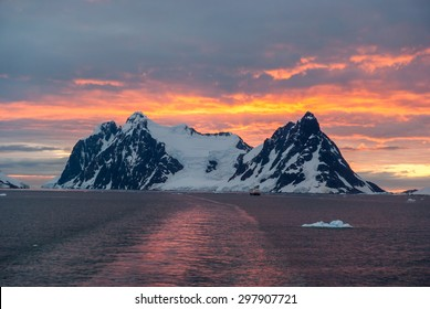 Cruise ship sailing through Lemaire Channel during stunning sunset, Antarctica