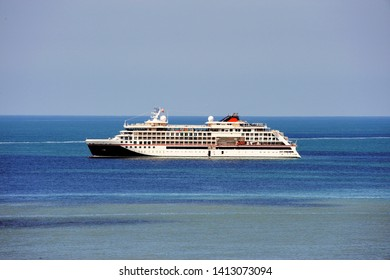 Cruise ship at sea, large luxury white cruise ship on blue sea water and blue sky background.