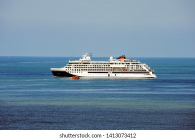 Cruise ship at sea, large luxury white cruise ship on blue sea water and blue sky background.Small watertaxi transporting passengers to the shore