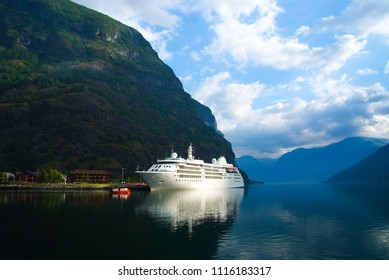 Cruise ship in sea port on mountain landscape in Flam, Norway. Ocean liner in sea harbor with green mountains. Cruise destination and travel. Summer vacation and holiday. Wanderlust and discovery.