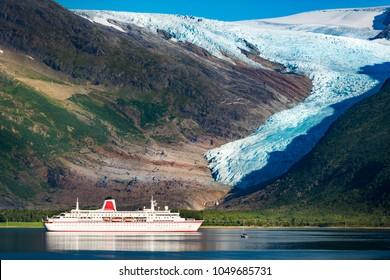 Cruise ship at Svartisen glacier in Norway, Scandinavia, Europe. Travel by water. Mountain in background.