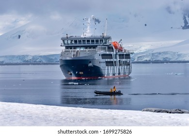 Cruise Ship Tourists Rubber Boat Snow Mountains Blue Glaciers Damoy Point Antarctic Peninsula Antarctica.  Glacier ice blue because air squeezed out of snow.