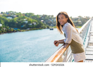Cruise ship vacation Asian woman relaxing on deck enjoying view from boat of port of call city on St. Lucia island in the Caribbean. Happy casual tourist girl outside on tropical holiday destination.