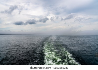 Cruise ship wake trail against hazy horizon with clouds.