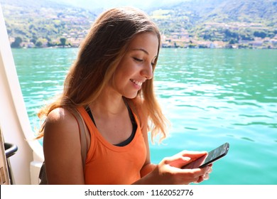 Cruise ship woman using mobile phone on travel vacation. Girl texting sms or using Wifi Internet. Tourist looking at her holidays pictures.