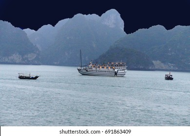 Cruise ships anchor at twilight with karst islands in background  in Halong Bay, Gulf of Tonkin,  Vietnam