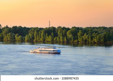 Cruise tourist boat moving on Dnieper river in Kiev, Ukraine. Beautiful sunset colors