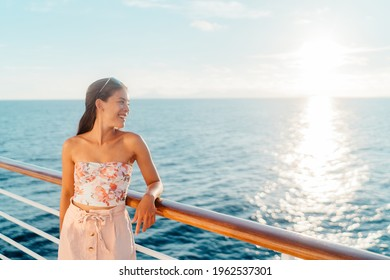 Cruise travel vacation Asian young woman looking at ocean watching sunset from balcony deck. Happy tourist lady relaxing on holidays