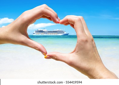 Cruise vacation. Cruise ship in the sea near the tropical island inside hands making a heart shape. Tropical Resort. Vacation concept. Summer holidays. Tourism.