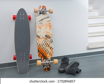 A cruiser skateboard and a drop through longboard are leaning against a white wall in a modern apartment with two black suede sneakers next to it. Location shot with copy space, no people.