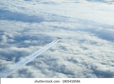 Cruising airline commercial jet with contrails over pastel colored clouds.
