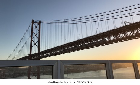 Cruising in the Atlantic ocean by sunset and sunrise near to Lisbon Portugal bridge of the 25th April