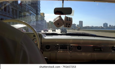 Cruising the Malecon, Cuba in a vintage car.  View over the dashboard of a classic car travelling the seawall in Havana.