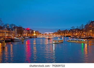 Cruising on the river Amstel in Amsterdam at the Tiny Bridge at sunset in the Netherlands